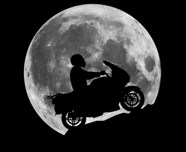 A motorcycle silhouetted against a full moon