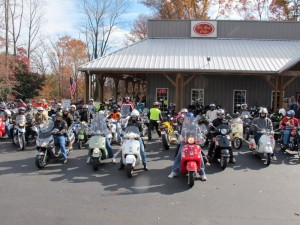 A large group of scooters pose for a photograph before a group ride