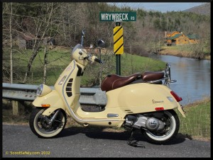 Scooter next to a road sign reading WhyWreck Rd